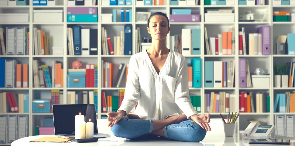 Relaxed woman practicing meditation at home at night, she is sitting in the lotus position on the office desk