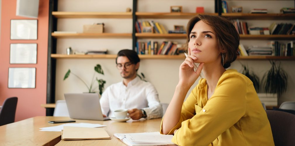 Young pensive woman sitting at the table with notepad dreamily thinking with colleague in office